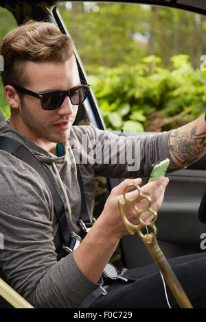 Portrait of man driving wearing sunglasses and using smart phone - Stock Photo