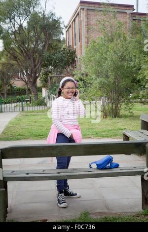 Young girl standing beside bench using mobile phone - Stock Photo