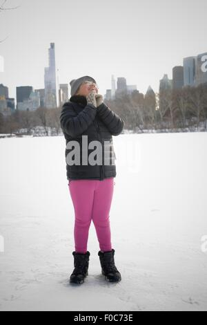 Young girl standing in snowy landscape, excited, New York, NY, USA - Stock Photo