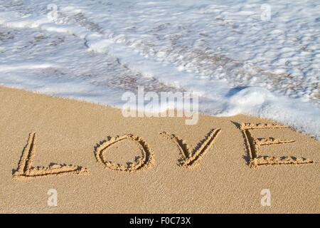 Love, written in sand, close-up - Stock Photo