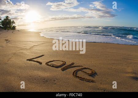 Love, written in sand, sunset - Stock Photo