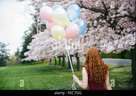 Rear view of young woman with long wavy red hair and bunch of balloons in spring park - Stock Photo