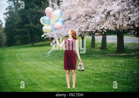 Young woman holding bunch of balloons in spring park - Stock Photo