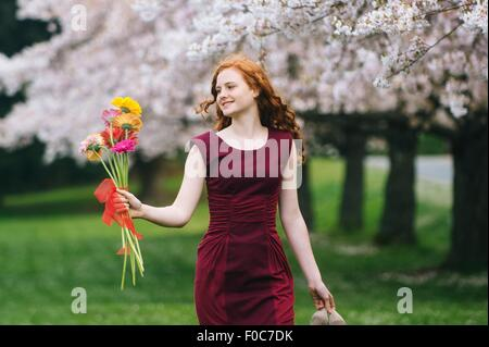 Young woman holding bunch of flowers in spring park - Stock Photo
