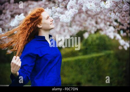 Portrait of young woman with long wavy red hair in spring park