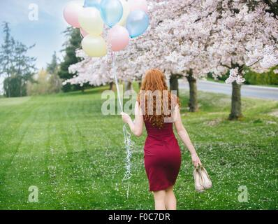 Rear view of young woman with long wavy red hair and bunch of balloons strolling in spring park - Stock Photo