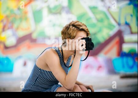 Stylish teenage girl photographing with camera in front of graffiti wall - Stock Photo