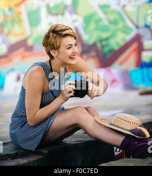 Stylish teenage girl sitting on sidewalk with camera in front of graffiti wall - Stock Photo