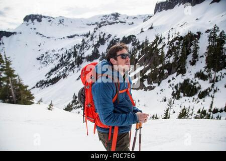 Young male skier looking out from mountainside, Mount Baker, Washington, USA - Stock Photo