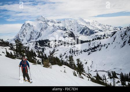 Young male skier moving along mountainside, Mount Baker, Washington, USA - Stock Photo