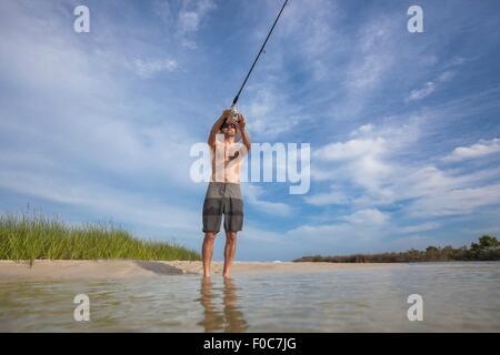 Low angle view of mature man fishing, Fort Walton, Florida, USA - Stock Photo