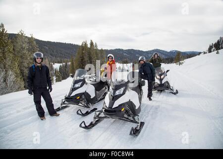 Friends on snowmobile, Jackson Hole, Wyoming - Stock Photo