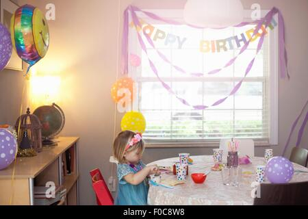 Portrait of blonde girl sitting at birthday party table - Stock Photo