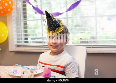 Boy in party hat sitting at table eating birthday cake pulling funny face - Stock Photo
