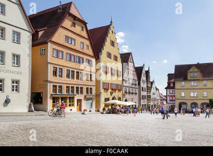 Tourists walking by typical buildings on the Marktplatz  Market Square, Rothenburg ob der Tauber, Franconia, Bavaria, - Stock Photo