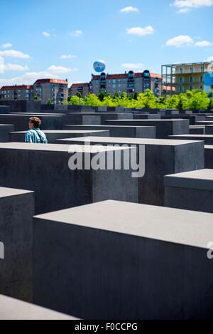 Woman walking through the Holocaust memorial, Berlin, Germany - Stock Photo