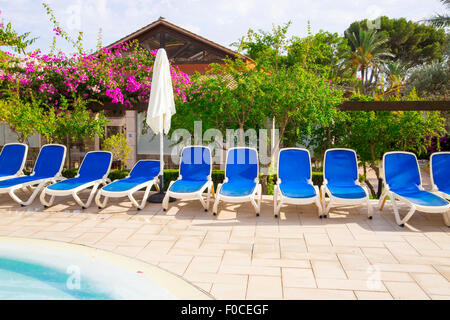Blue sun beds around a hotel swimming pool - Stock Photo