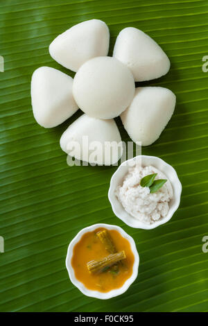 Fresh steamed Indian Idly (Idli) arranged decoratively as a flower on traditional banana leaf. Served with chutney - Stock Photo
