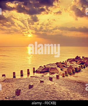 Retro toned dramatic sunset over beach and rocky pier. - Stock Photo