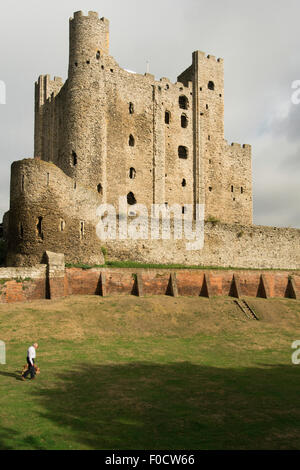 Old man walking dog in the moat of Rochester Castle in Kent, England, UK - Stock Photo