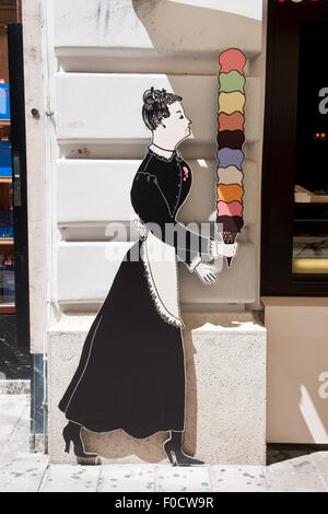 Advertising board of a woman in an old fashioned maid costume carrying ice cream outside the Demel pastry shop in - Stock Photo