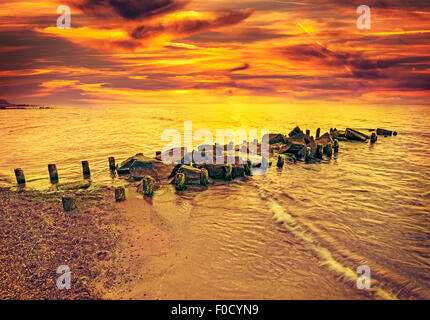 Vintage toned dramatic sunset over beach and rocky pier. - Stock Photo
