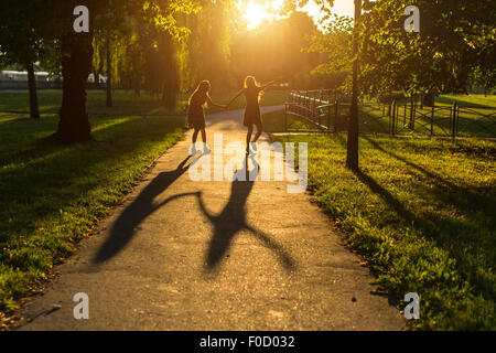 Silhouettes of two girls walking down the alley holding hands, during amazing sunset. - Stock Photo