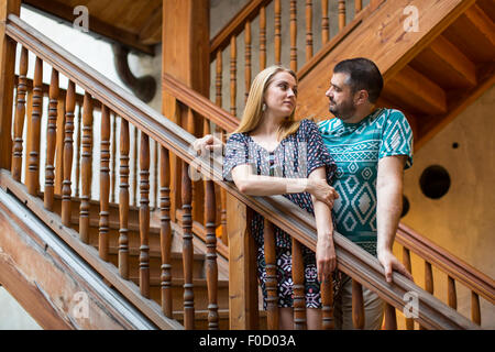 Couple in love standing on the old wooden staircase. - Stock Photo