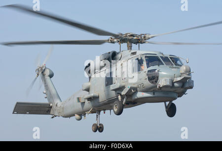 An MH-60R Seahawk assigned to Helicopter Maritime Strike Squadron 46 (HSM-46), in flight over the Persian Gulf while - Stock Photo