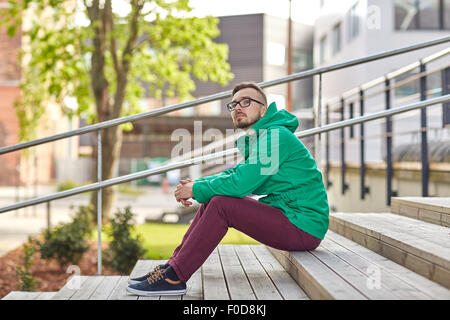 happy young hipster man sitting on stairs in city - Stock Photo