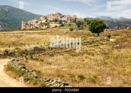 A winding dirt track leads to the picturesque village of Sant'Antonino in the Balagne region of Corsica - Stock Photo