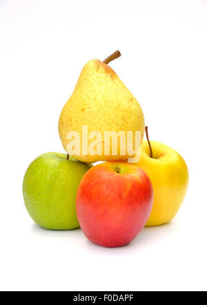 Pear balances on top of three types of apples - Stock Photo