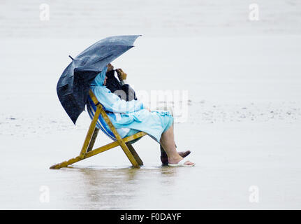 A man and a woman sitting in deck chairs. on a beach in rain coats during a heavy rain storm inclement summer weather - Stock Photo