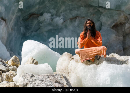 A Sadhu, holy man, is sitting and praying in lotus pose, padmasana, on a block of ice at Gaumukh, the main source - Stock Photo
