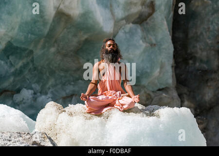 A Sadhu, holy man, is sitting and meditating in lotus pose, padmasana, on a block of ice at Gaumukh, the main source - Stock Photo