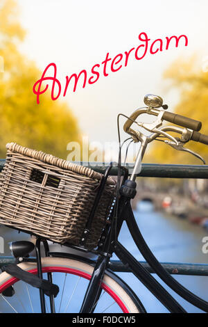 Closeup of a nostalgic bicycle parked at a handrail on a canal bridge and red nostalgic written name Amsterdam - Stock Photo