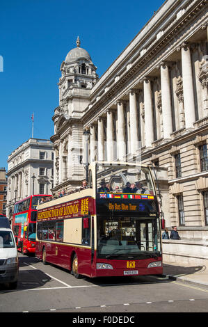 Open top sightseeing bus touring the City of London, England. - Stock Photo