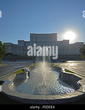 Fountain on Unirii Boulevard with Parliament and evening sun as backdrop - Stock Photo