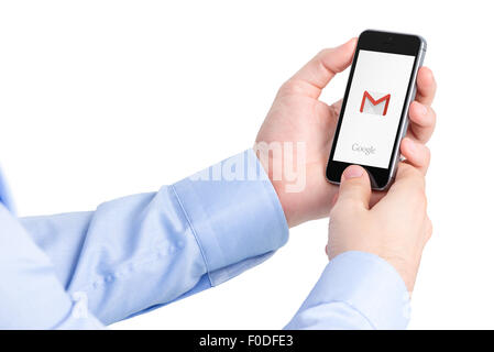 Varna, Bulgaria - May 29, 2015: Man holding Apple iPhone with Google Gmail application logo on the screen. - Stock Photo