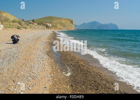 Wild pebbly beach on a Black Sea shore on Meganom cape - Crimean peninsula - Stock Photo
