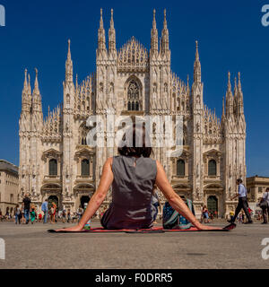 Female tourist sitting on a picnic blanket, on the ground outside Milan Cathedral. Italy - Stock Photo