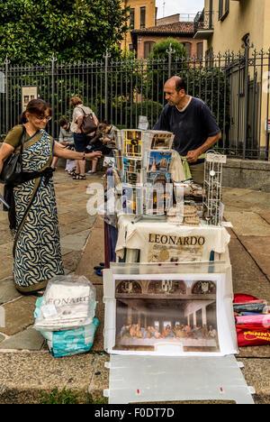 Man selling postcards of the Last Supper prints by Leonardo da Vinci's  outside the Santa Maria delle Grazie church - Stock Photo