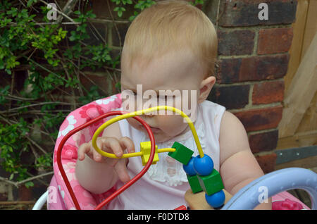 A ten month old baby playing out doors with a colorful Bead Maze. - Stock Photo