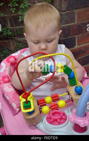 A ten month old baby playing out doors with a colorful Mini Bead Maze. - Stock Photo