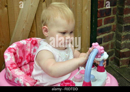 A ten month old baby playing with great concentration out doors on her interactive play wheelie. - Stock Photo