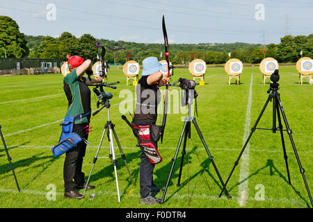 Two women archers in line shooting different styles of modern bows (compound and recurve) in competition, West Yorkshire, - Stock Photo