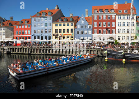 Canal tour boat turning around in crowded Nyhavn canal on a warm and sunny summer day full of tourists and visitors. - Stock Photo
