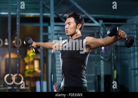 Young man lifting weights at gym - Stock Photo