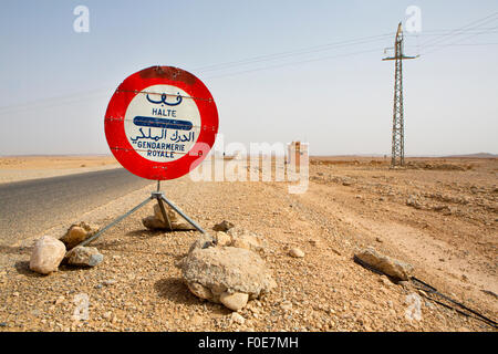 Red Stop Police sign against a blue sky on the road to Ouarzazate in Morocco. The text is written is Arabic and - Stock Photo