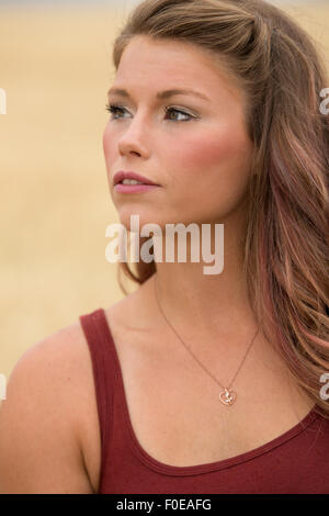 Young woman posing in large wheat field wearing red tank top. - Stock Photo